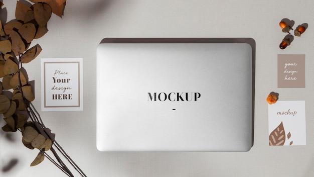 Draufsicht geschlossener laptop mit modell mit blättern