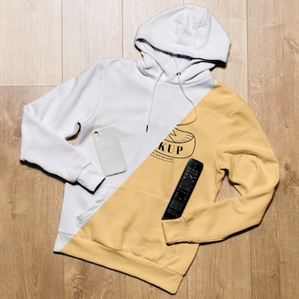Draufsicht hoodie modell mit telefonhülle und tv-fernbedienung