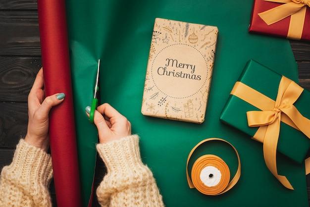 Draufsicht von den händen, die weihnachtsgeschenke einwickeln
