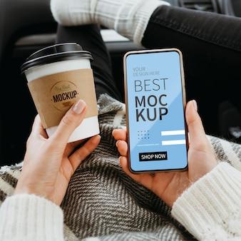 Draufsicht zur hand mit smartphone-modell und tasse kaffee