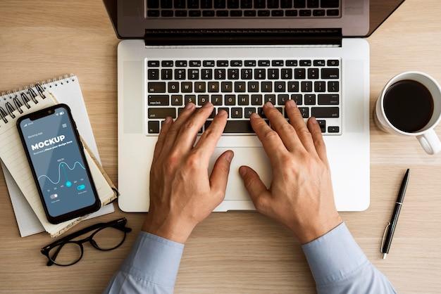 Draufsichtmann, der laptop nahe telefonmodell verwendet