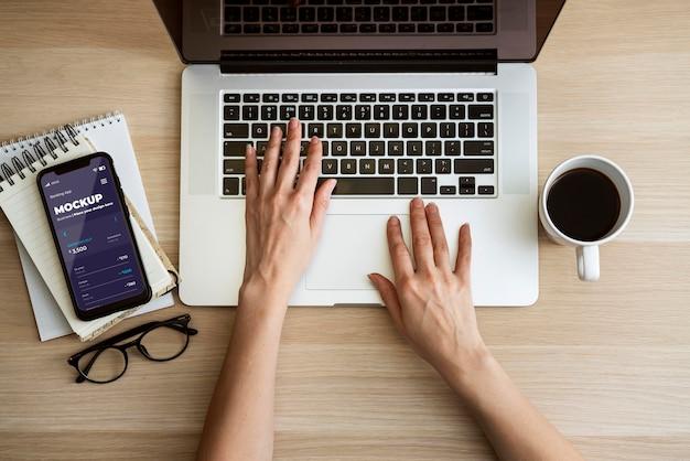 Draufsichtperson, die laptop nahe telefonmodell verwendet