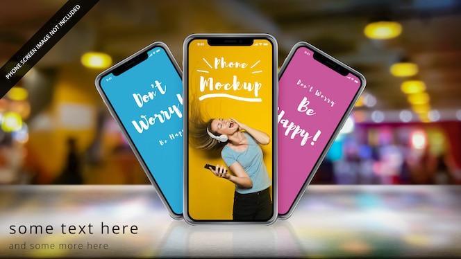 Drei apple iphone x auf einer reflektierenden oberfläche mit bokeh