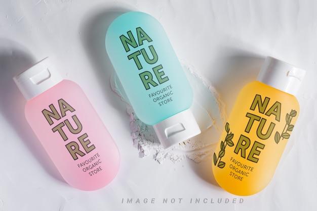Drei kosmetikflaschen modell auf pulver