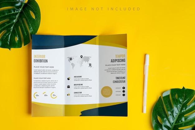 Dreifach gefaltetes broschürenmodell auf gelbem hintergrund