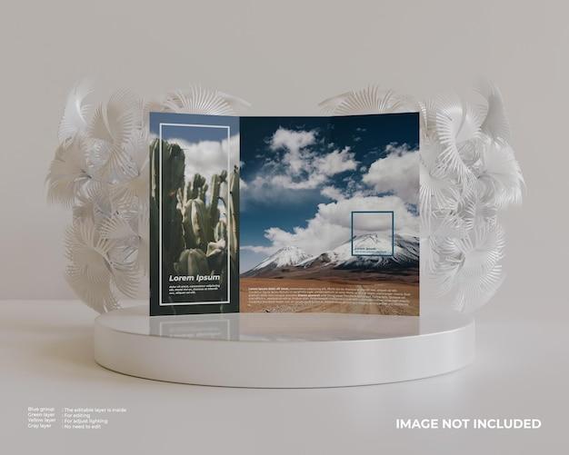 Dreifach gefaltetes broschürenmodell mit podium und weißer pflanze hinten