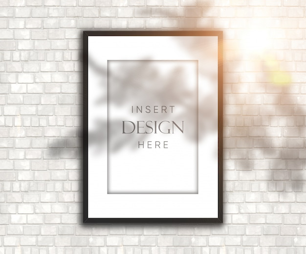 Editable leerer bilderrahmen auf backsteinmauer mit schatten- und sonnenscheinüberlagerung