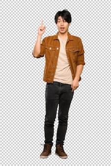 Ein in voller länge schuss eines asiatischen mannes mit brauner jacke, die beabsichtigt, die lösung beim anheben eines fingers zu verwirklichen