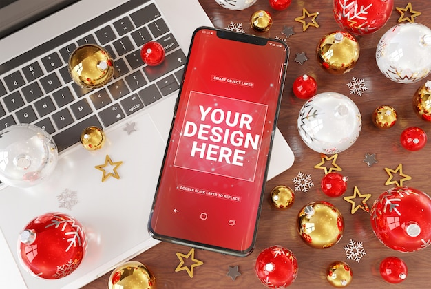 Ein modell von smartphone auf dem desktop mit laptop und christbaumkugeln