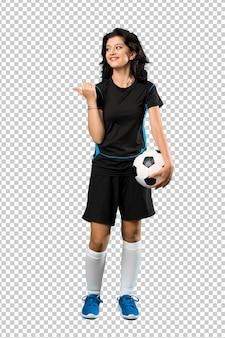 Ein schuss in voller länge einer jungen fußballspielerfrau, die auf die seite zeigt, um ein produkt darzustellen