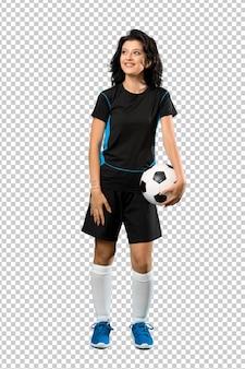 Ein schuss in voller länge einer jungen fußballspielerfrau, die oben beim lächeln schaut
