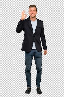 Ein schuss in voller länge eines blonden gutaussehenden mannes, der okayzeichen mit den fingern zeigt