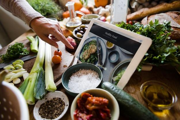 Eine digitale tablette in der mitte einer belebten küchenbank
