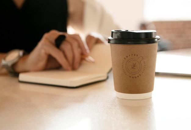 Eine einweg-kaffeetasse auf dem tisch