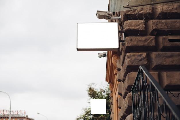 Eine werbetafel, modell, von der seite eines gebäudes draußen vor einem wunderschönen blauen himmel