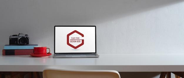Einfacher arbeitsplatz mit mockup laptop und bücher mit kamera