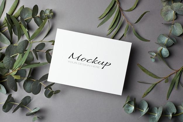 Einladungs- oder grußkartenmodell mit eukalyptuszweigen auf grau