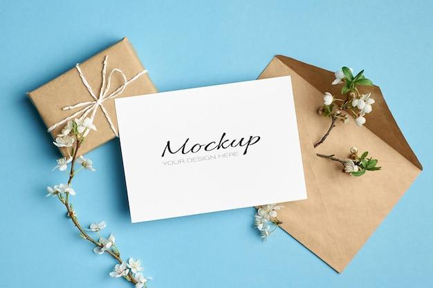 Einladungs- oder grußkartenmodell mit geschenkbox, umschlag und kirschbaumzweigen mit blumen