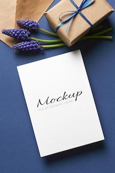 Einladungs- oder grußkartenmodell mit geschenkbox und blauen muscari-blumen