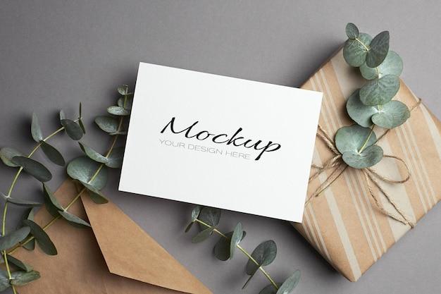 Einladungs- oder grußkartenmodell mit geschenkbox und frischen eukalyptuszweigen auf grau