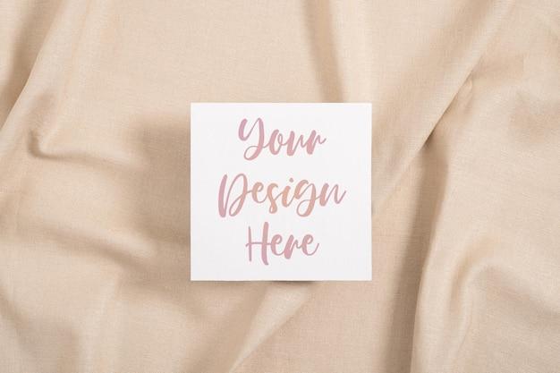 Einladungskartenmodell des weißen quadrats auf beiger textiloberfläche