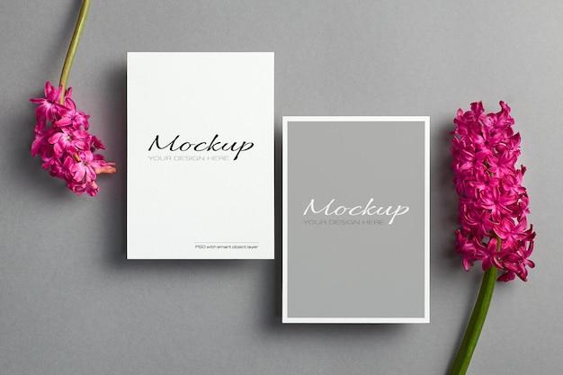 Einladungskartenmodell mit vorder- und rückseite auf grauem hintergrund mit hyazinthenblumen