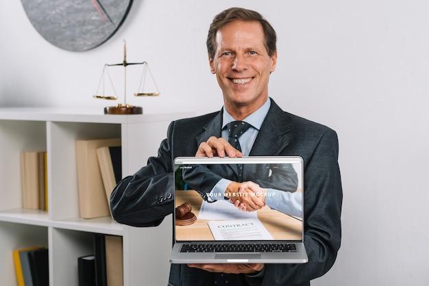 Eleganter geschäftsmann, der laptopmodell darstellt