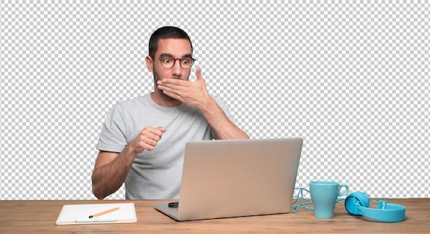 Entsetzter junger mann, der an seinem schreibtisch sitzt