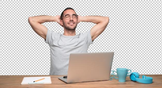 Entspannter junger mann, der an seinem schreibtisch sitzt