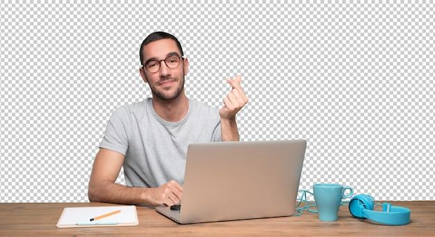 Erfüllter junger mann, der an seinem schreibtisch sitzt und eine geste des geldes mit seiner hand tut