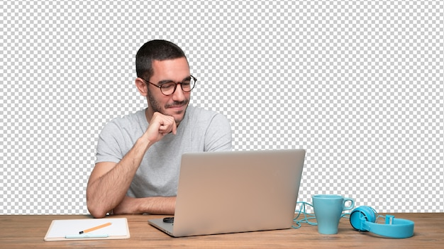 Erfüllter junger mann, der an seinem schreibtisch sitzt