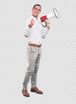 Erfüllter junger mann, der ein megaphon - vollen körperschuß verwendet