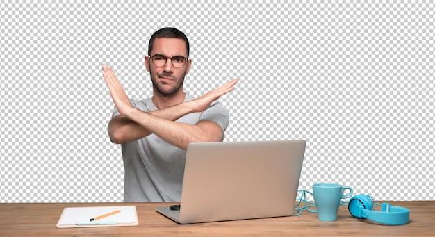 Ernster junger mann, der an seinem schreibtisch sitzt und eine geste des nicht kreuzes tut