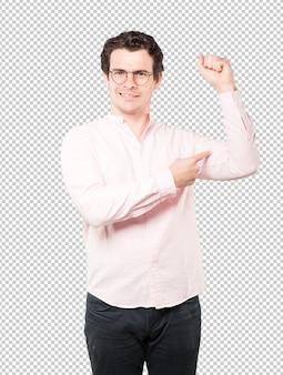 Ernster junger mann, der eine geste der stärke bildet