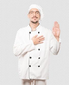 Ernsthafter junger koch mit einer geste des eides