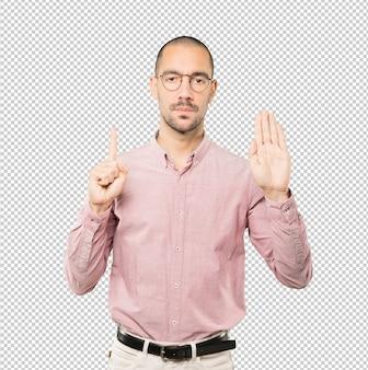 Ernsthafter junger mann, der mit seiner handfläche eine geste des stopps macht