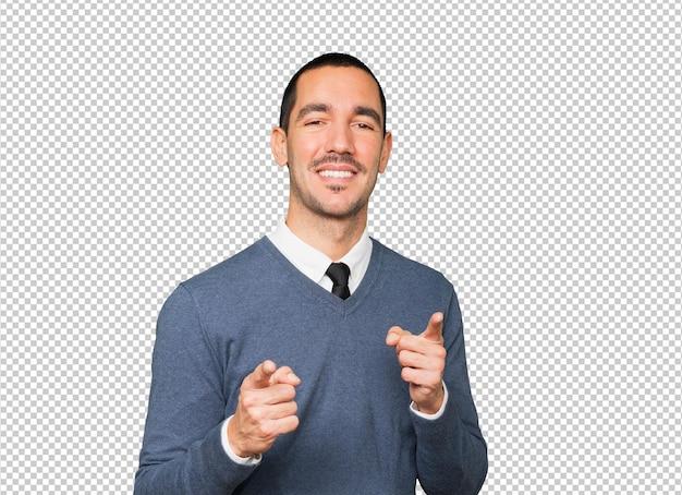 Erstaunter junger mann, der mit seinem finger auf sie zeigt
