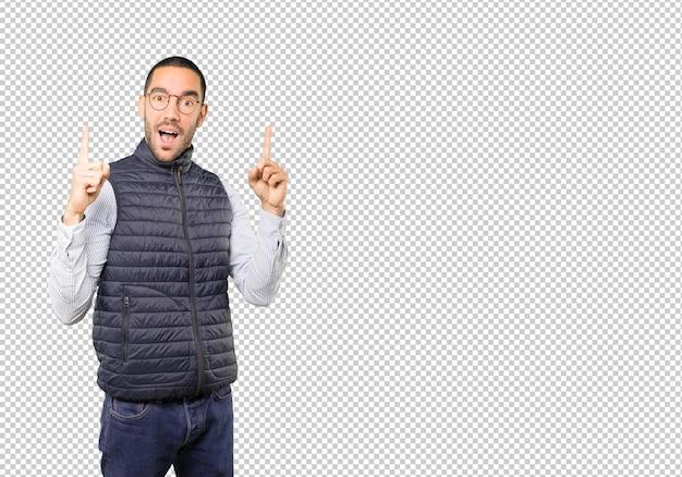 Erstaunter junger mann, der mit seinem finger nach oben zeigt