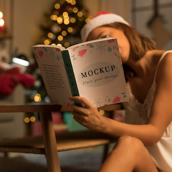Erwachsene frau, die ein weihnachtsbuch mit modell liest