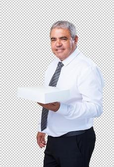 Fälliger mann, der einen weißen kasten anhält