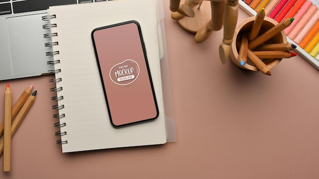 Femininer arbeitsbereich mit smartphone-notebook-malwerkzeugen und laptop im home office