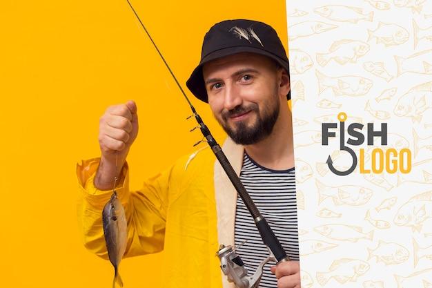 Fischer im regenmantel, der einen fisch hält