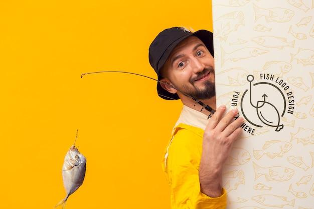 Fischer im regenmantel versteckt sich hinter modellkarte
