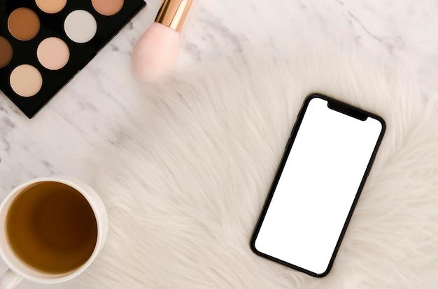 Flach gelegtes smartphone-modell mit make-up-palette