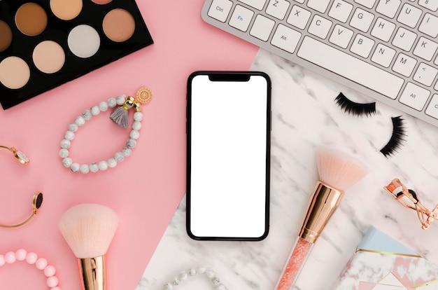 Flach gelegtes smartphone-modell mit make-up-pinseln auf dem schreibtisch