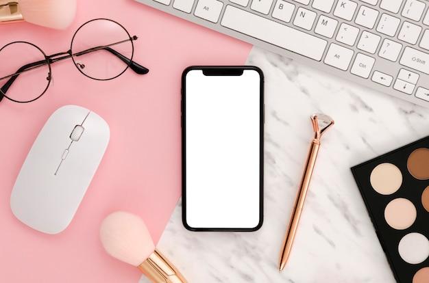 Flach gelegtes smartphone-modell mit make-up-zubehör auf dem schreibtisch