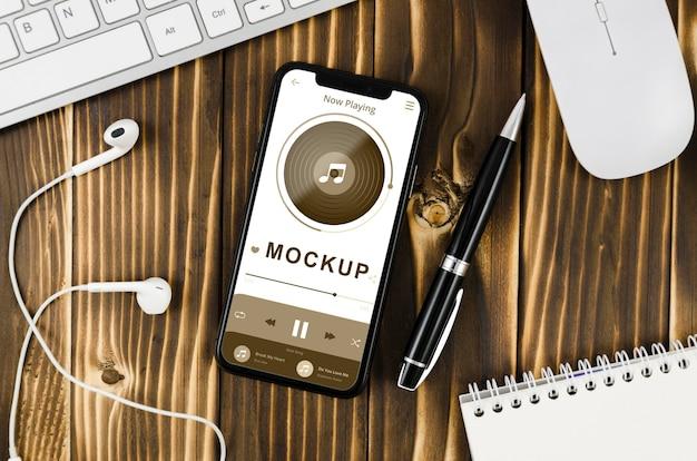 Flach gelegtes smartphone-modell mit stift und kopfhörern