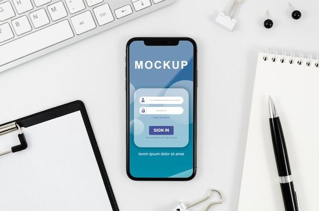 Flach gelegtes smartphone-modell mit zwischenablage und stift auf dem schreibtisch