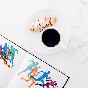 Flach lag offenes buchmodell mit kaffee und croissant auf