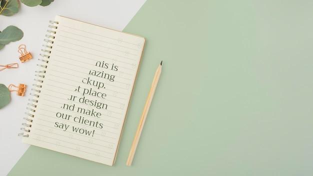 Flach liegendes notizbuch und pflanze mit kopierraum